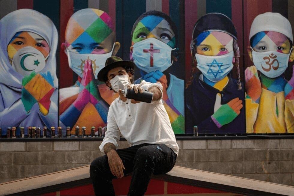 Eduardo Cobra em frente ao painel Coexistência, que mostra crianças de diversos países usando máscaras e juntando as mãos, em sinal de oração